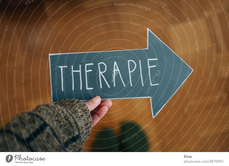 A person holds an arrow with the word therapy. Concept Psychotherapy for mental illness, such as depression, anxiety disorders and addiction problems. Therapy