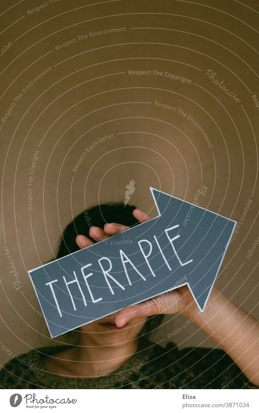 A woman is holding an arrow marked therapy. Concept Psychotherapy for mental illness, such as depression, anxiety disorders and addiction problems. Therapy Help