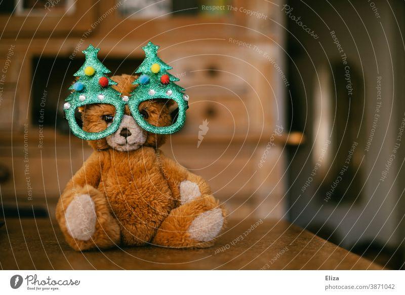 A teddy bear with Christmas tree glasses. Concept Christmas with children. Teddy bear cuddly toy Infancy Christmassy Cap Christmas & Advent Bear material