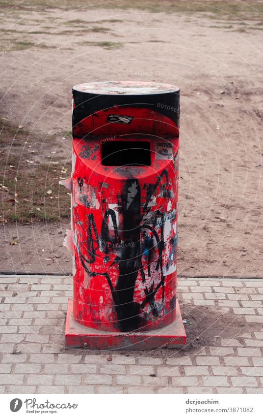A beautiful red iron litter bin with front throw-in.  Somewhat smudged with black paint, standing lonely and abandoned on the sidewalk. The word NO can still be seen.