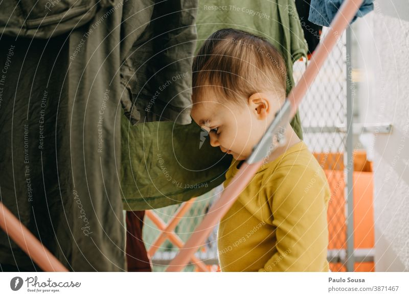 Toddler playing with clothes on the clothesline 0-09 years Lifestyle affectionate at home authentic autumn caring casual caucasian child color curiosity day