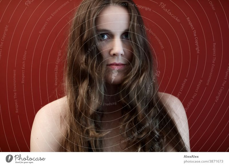 Portrait of a young woman in front of a red wall Woman Slim pretty Brunette long hairs Shoulder Face smart emotionally Skin see look Looking Direct naturally