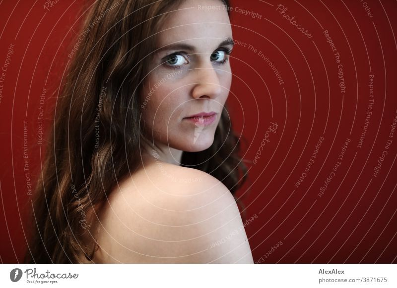 Lateral portrait of a young woman in front of a red wall Woman Slim pretty Brunette long hairs Shoulder Face smart emotionally Skin see look Looking Direct