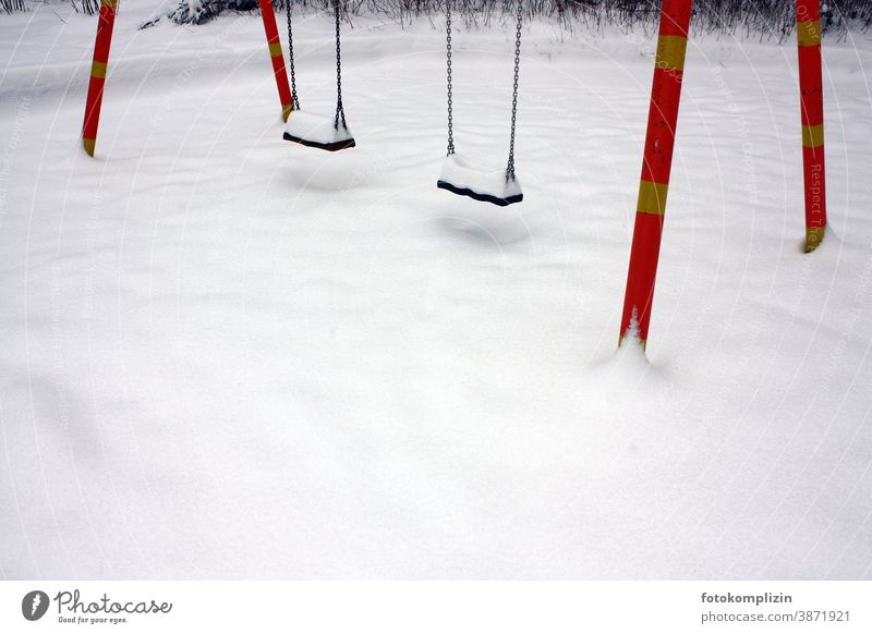 empty playground with two swings in the snow snowed over snowy Snow Winter White Playground Winter sports childcare Swing Snow layer tracks in the snow Lonely