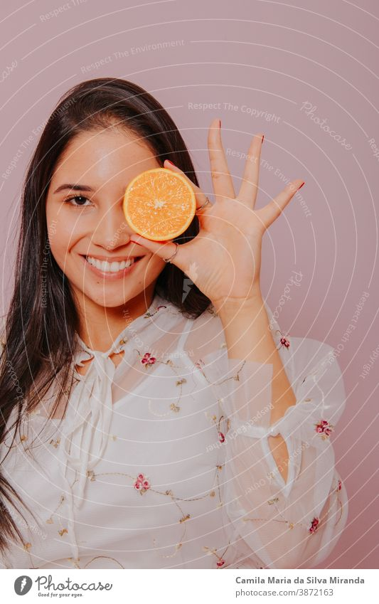 Model holding an orange. Studio shot with pink background. beautiful beauty care citrus closeup cosmetics face fashion fresh fruit girl glamour hair hairstyle