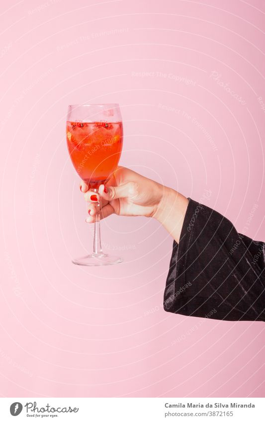 Female hand holding cup with red drink. Pink background. lifestyle closeup fresh woman citrus celebration cocktail holiday summer vacation young copy space