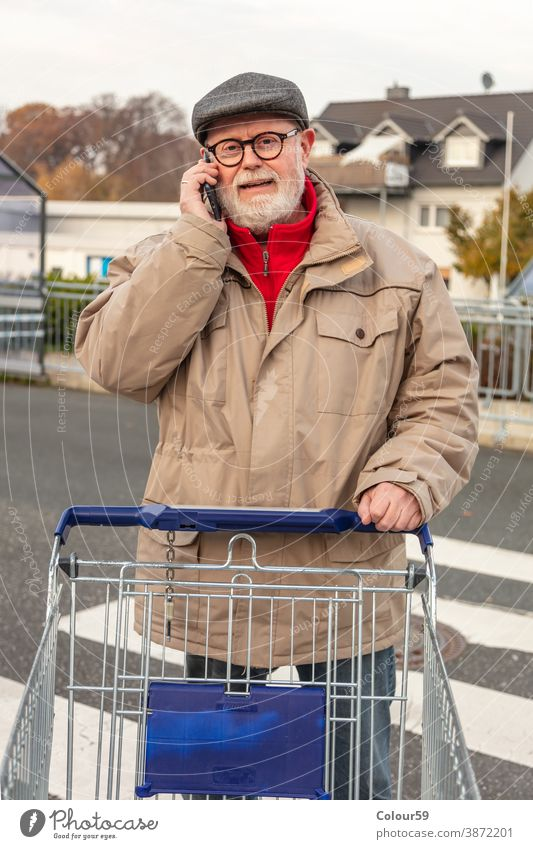 Senior with winter cloth using cell phone consumer pay mall attractive shopper outdoors lifestyle market person smartphone cellphone young buy holding cart