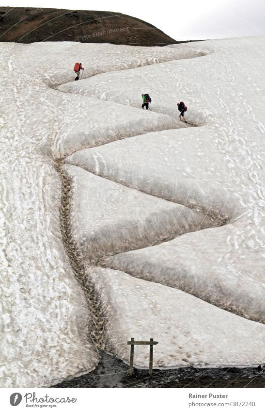 Three hikers on a winding path in Iceland with traces of a shortcut taken by other hikers serpentine road zig zag concept upward activity adventure backpack