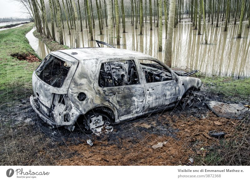 burnt out car abandoned near a flooded poplar grove danger smoke fire accident trouble hot flammable pollution rubbish vandalism land vehicle exploding
