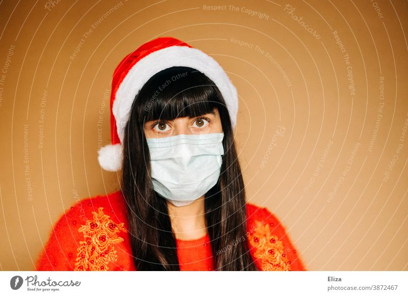 Young woman in christmassy clothes is wearing a mouth guard and a Santa cap. Christmas during the Corona Pandemic. Mask Disposable mask Christmas mood