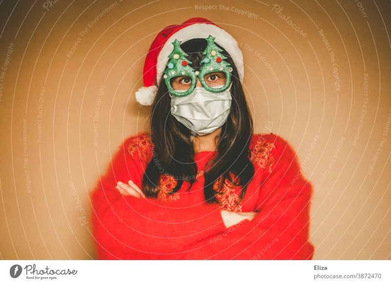 Young woman in christmassy clothes wears mouth guard and crosses her arms in front of her breast Christmas Christmassy Sweater Red Santa's cap