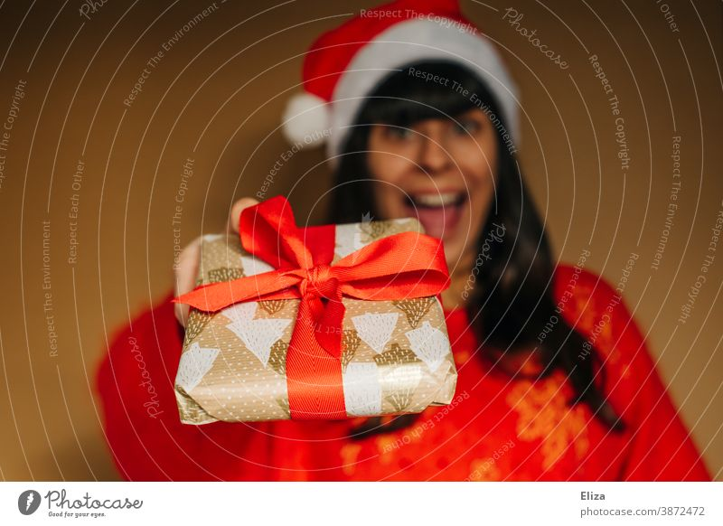 Woman in Santa's cap joyfully presents a Christmas present Christmas gift Donate Santa Claus hat Giving of gifts Joy Euphoric excited Christmas & Advent Gift