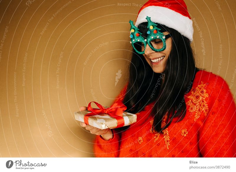 Young woman in christmassy clothes looks smiling at a christmas present Christmas Woman Christmas gift garments Sweater Red Gift Giving of gifts Donate get Joy