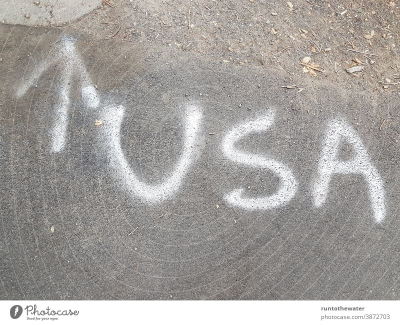 USA letters on the street Arrow Street Clue Direction Trend-setting North United States united states of america Americas American urban travel Concrete