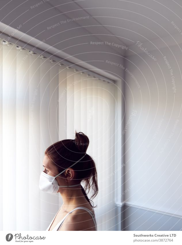 Young woman looking out of window wearing protective face mask. female home virus disease diseases flu air health sick prevention inside outside isolation self