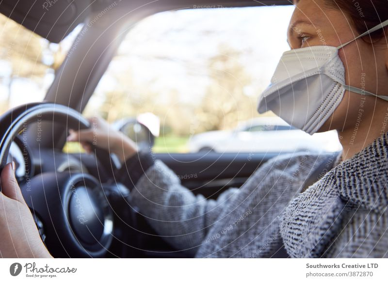 Young woman wearing protective mask driving car caucasian young female steering vehicle horizontal face person adult drive millennial young adult steering wheel