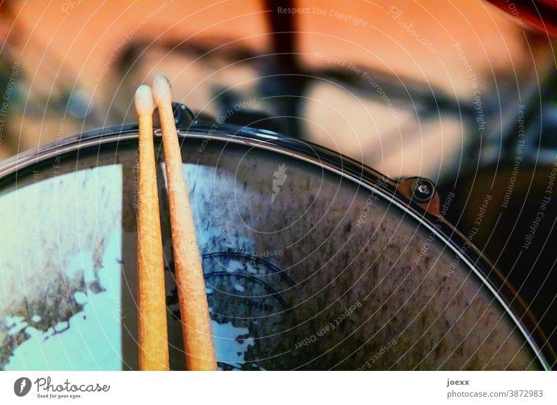 Drumsticks rest on snare drum with heavily worn skin, weak depth of field play drums Break wooden sticks Tympanic membrane Snare Pelt Drum set Rhythm