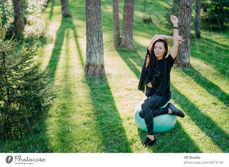 Photo of active flexible brunette woman stretches with fitball, does pilates or fitness exercises, poses on green grass during sunny spring day in forest, enjoys gymnastic exercises on fresh air.