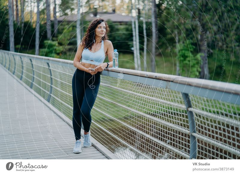 Serious thoughtful woman with spoty body, dressed in cropped top and leggings, poses at bridge looks pensively away, listens music in earphones. People, healthy lifestyle and fitness concept