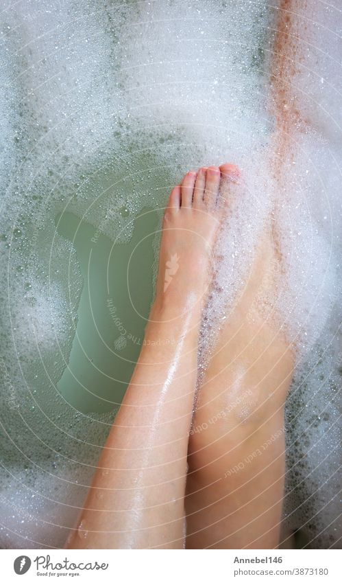 Women's legs in the bathtub, bathing with bubble bath foam top view, relaxtion beauty spa concept care hygiene soap body young bathroom relaxation water female
