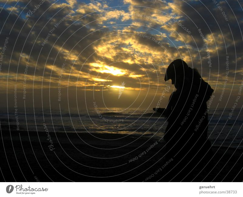woman against light Waves Coast Beach Sunset Twilight Cloud formation Reflection Back-light Silhouette Woman Cap Hooded (clothing) Looking Appraise Think Touch
