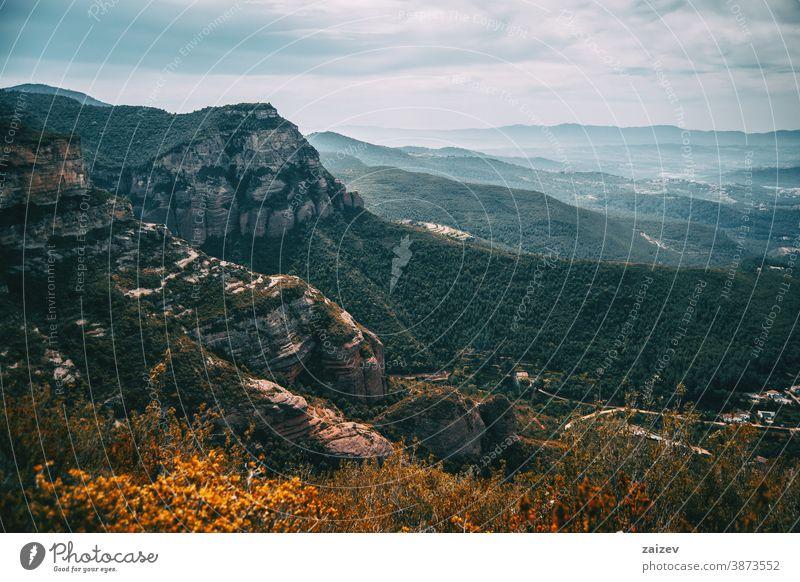 An imposing landscape of rugged mountains and fields that extend to the horizon Cingles de Bertí Riscos de Berti sant miquel del fai trees grove nature