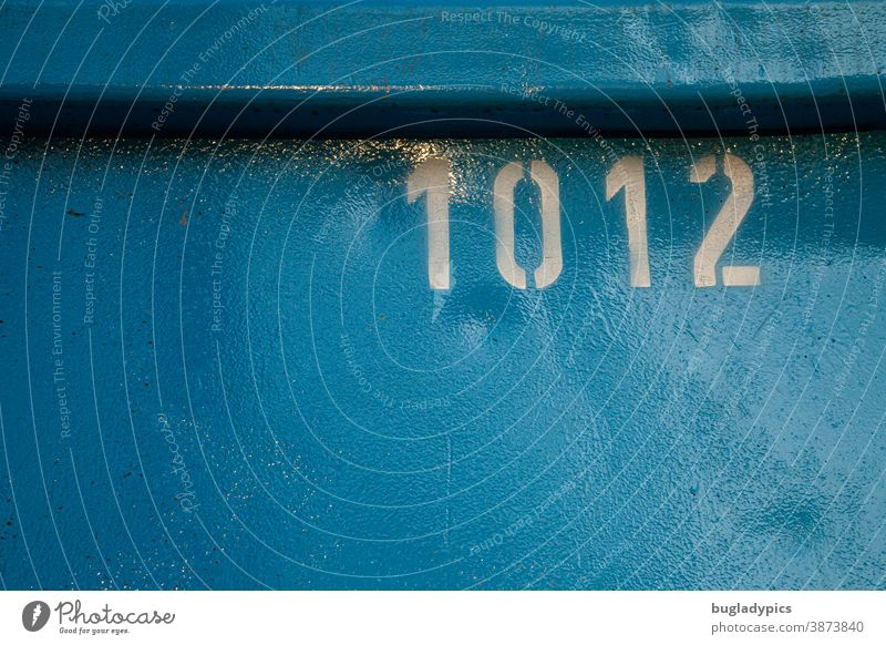 White number 1012 on blue metal background figures Digits and numbers Characters Signs and labeling Blue Container Numbers Metal Lettering Screen print