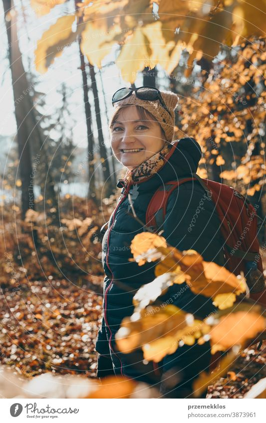 Woman with backpack wandering in a forest on autumn sunny day active activity adventure backpacker destination enjoy exploration explore fall female hike hiker
