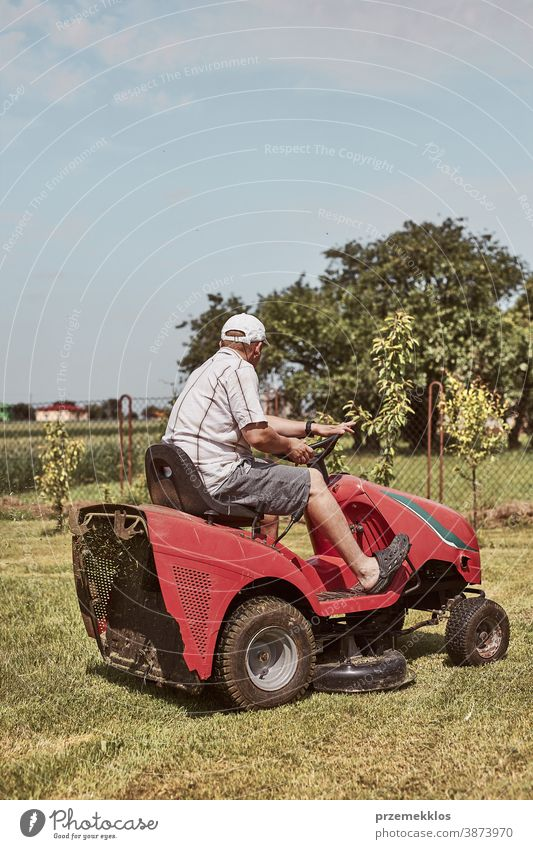 Man mowing his lawn using riding lawnmower occupation seasonal cut trimming man job person field professional ride gardener drive equipment worker male