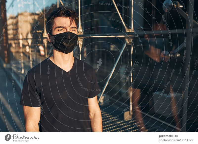 Young man walking in the city center along glass store front wearing the face mask to avoid virus infection boy care caucasian contagious conversation corona