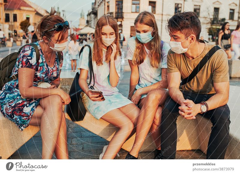 Young women spending time together sitting in the city center wearing the face masks to avoid virus infection caucasian conversation covid-19 female lifestyle