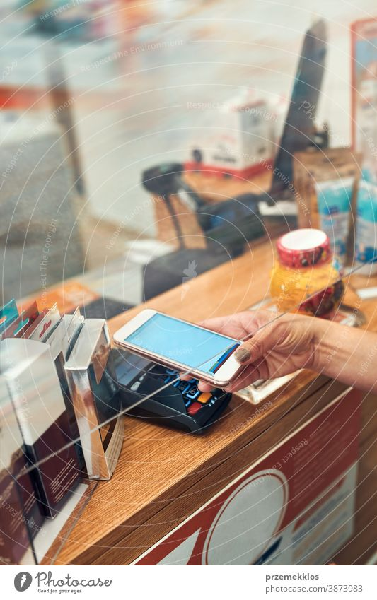 Woman paying for medicines at pharmacy using contactless method of payment via mobile phone woman chemist shop pandemic female care medical drugstore medication