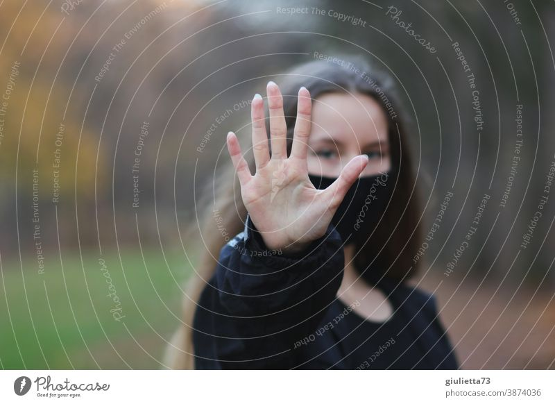 Teenage girls symbolizes: No - stop - stop by reaching out her hand in front of her Hold Hand gap Protection Looking into the camera Front view Upper body