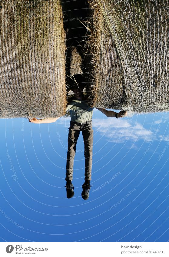 The hay bale carrier Hay bale Flying Boy (child) Superman Blue Sky On the head Distorted Hercules inverted world