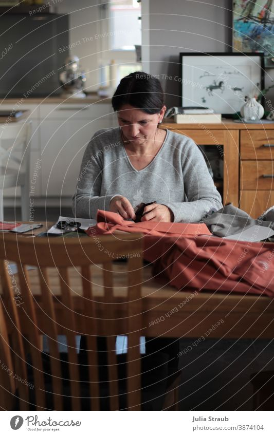 Amateur seamstress sits concentrated at the dining table Dinner table Tailoring Cloth coral natural light Claw fabric scissors Fashion textile Thread Creativity