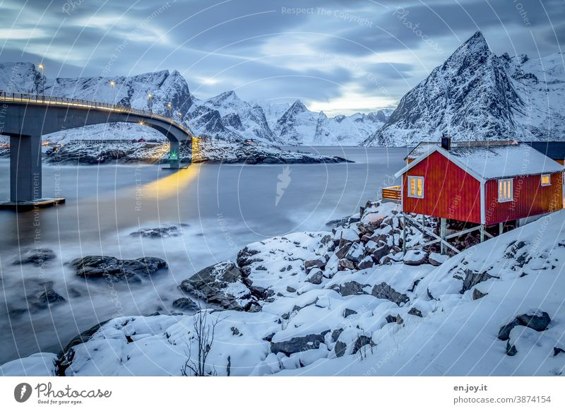 Red wooden house with a view of the Reinefjord and bridge in winter with lots of snow at the blue hour Lofotes Hamnøy Norway Scandinavia North Hut Vacation home