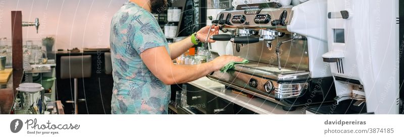 Young waiter cleaning the coffee machine cloth morning coffee shop cafe banner web header panorama panoramic unrecognizable professional service espresso