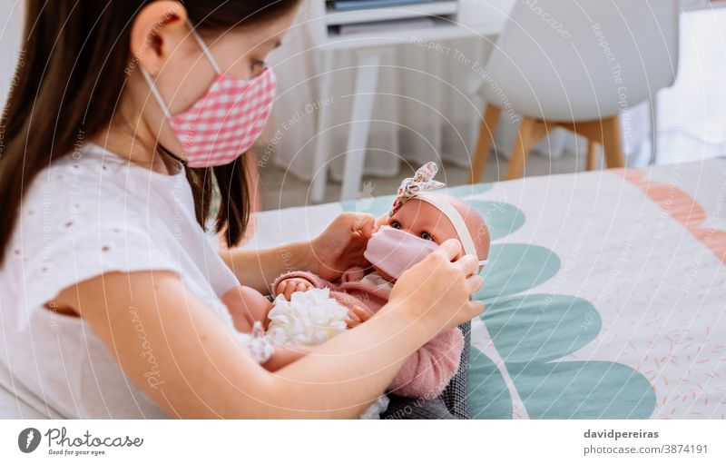 Girl with mask putting small mask on her doll girl playing putting mask face covid-19 coronavirus generation care people lockdown child female health protective