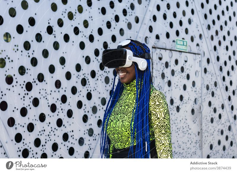 Black woman in VR headset in city vr virtual reality interact experience goggles street female ethnic black african american blue hair braid hairstyle trendy