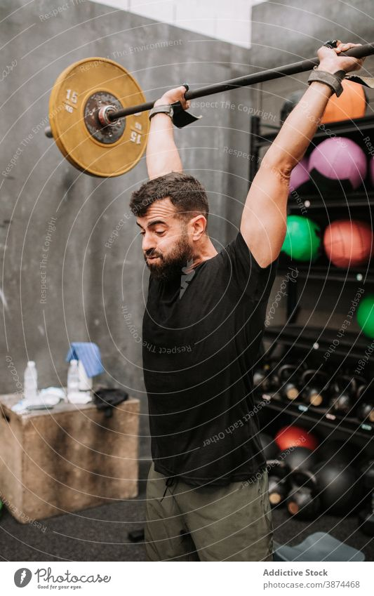 Strong man doing weightlifting exercises with barbell clean and jerk workout athlete muscular power male healthy fit strength body effort strong wellness