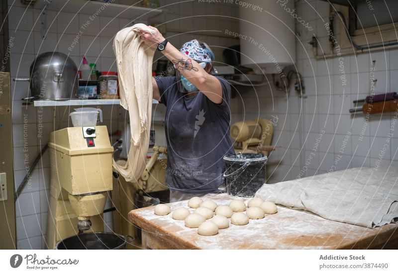 Woman kneading dough in bakehouse bread bakery raw work prepare kitchen female mask new normal cook food chef fresh culinary cuisine pastry ingredient recipe
