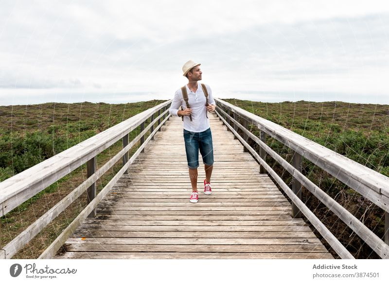 Male backpacker walking on wooden boardwalk traveler walkway man active nature explore adventure hike path journey vacation lifestyle activity summer holiday