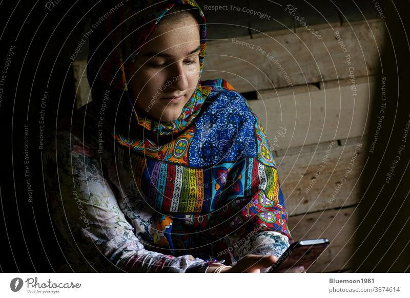 Portrait of an attractive teenage Muslim girl working with smart phone portrait white thinking bright casual people Caucasian cute dress healthy beauty lovely