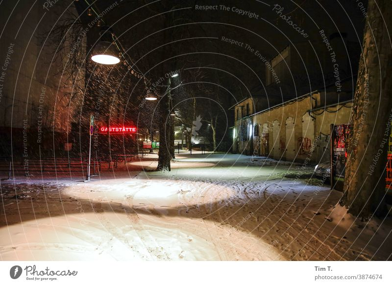 the entrance to the Prater beer garden with restaurant in winter . It is late evening and it is snowing . Berlin Restaurant chestnut avenue Prenzlauer Berg