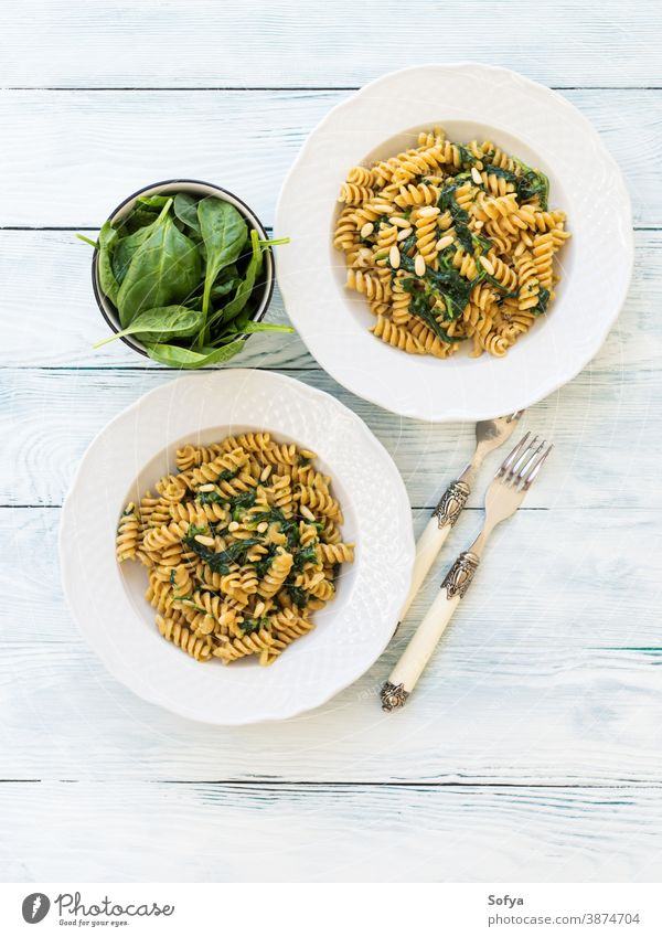 Whole grain pasta with spinach and pine nuts food plate table wood dish vegan vegetarian leaves italian baby meal rustic organic green gourmet cooking fusilli