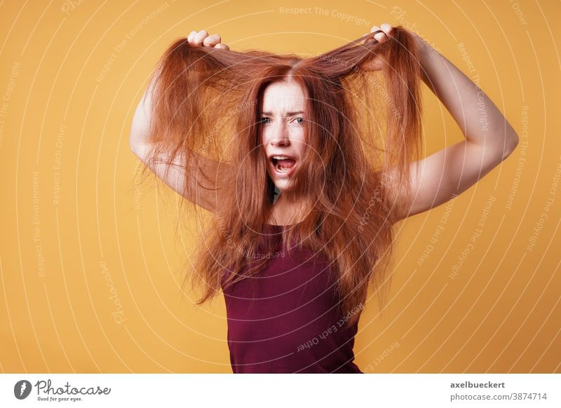 frustrated young woman pulling and tearing her hair bad hair day long red care frustration scream emotion messy unkempt disheveled tantrum funny hairstyle