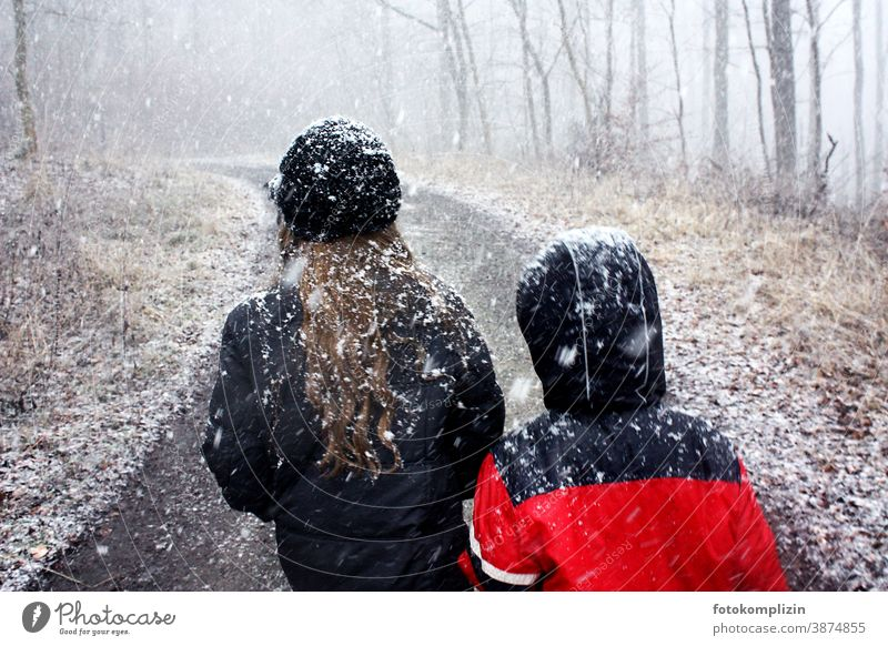 two children on a forest path while it is snowing Snowfall Snowflake Winter be a child onset of winter snowed over Infancy snowflakes Snowscape snowy