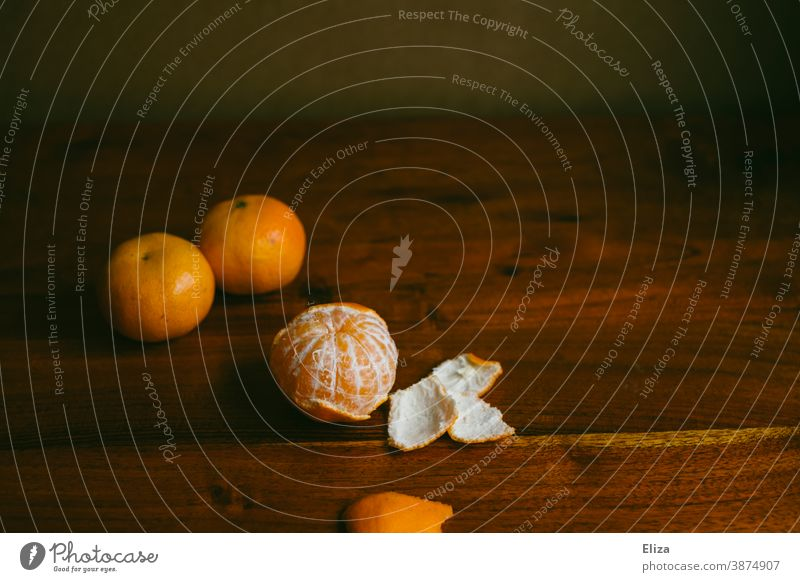 Three mandarins, one peeled, on a wooden table Table salubriously Winter Advent fruit Vitamin C Healthy Food Vitamin-rich Orange clementine Fresh Healthy Eating