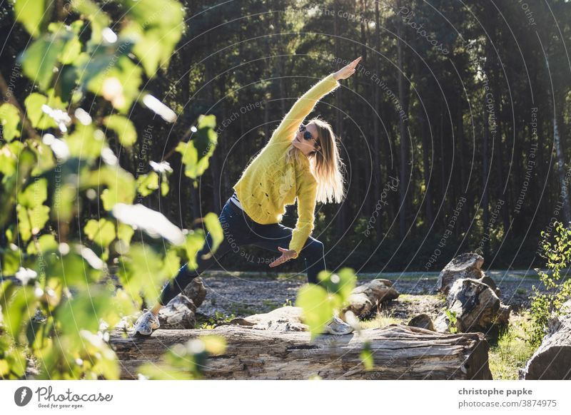 Woman doing yoga on a tree trunk in the forest Yoga Forest Tree trunk Green Environment Nature Exterior shot Colour photo Day Sports Movement leaves Landscape