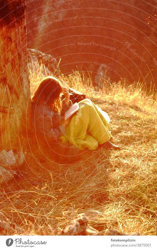 junge Frau, im Sonnenlicht an einen Stamm gelehnt, liest versunken in einem Buch Lesepause lesen Natur Feminine chill Break recover Lonely tranquillity
